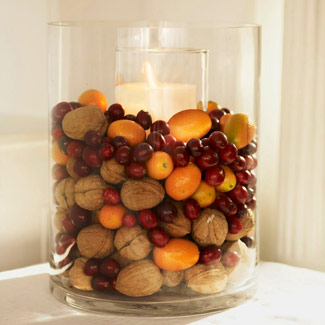 A hurricane candle filled with walnuts, kumquats, and cranberriers.